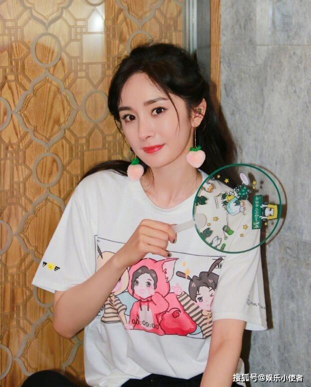 杨幂穿粉丝团会服拍照 手中拿着粉丝团的透扇十分宠粉