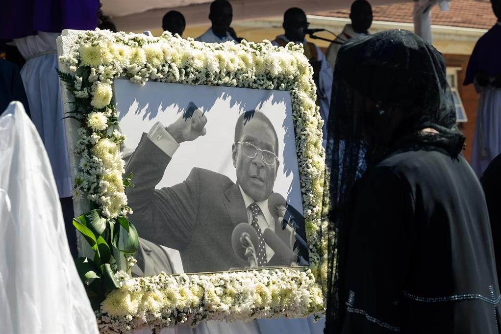 在津巴布韦西马绍纳兰省库塔马村,前总统罗伯特·穆加贝的遗孀格雷丝参加穆加贝安葬仪式时走过罗伯特·穆加贝的画像